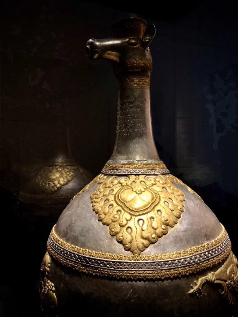 """2018年2月至7月,北京首都博物馆举办的""""天路文华——西藏历史文化展""""上的银壶,名为""""兽首胡人纹鎏金银瓶""""。(唯色拍摄)"""